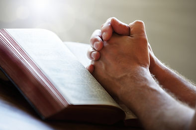 bigstock-Hands-folded-in-prayer-on-a-Ho-