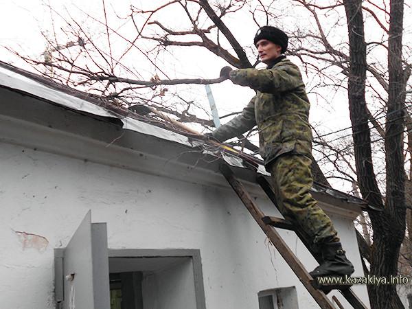 Старший урядник Пробатов расчищает крышу КПП от веток и листвы