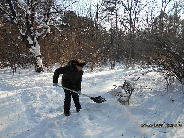 Сотник Карпенко расчищает пространство перед скамейками от снега