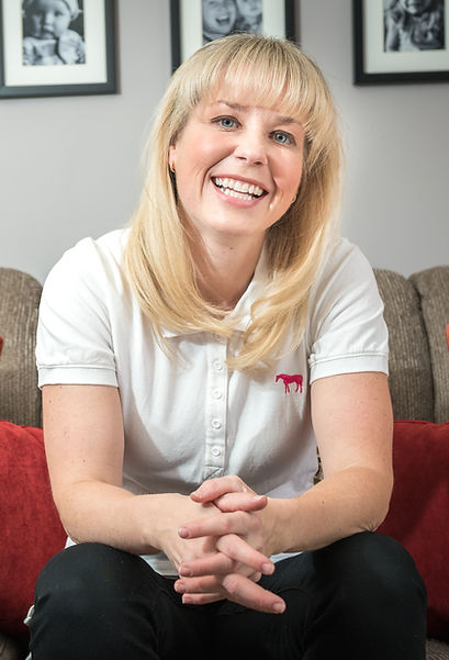 Shannon Rus, owner of Heavenly Homes, sitting on a couch smiling