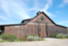 Image of the Mckenzie-Mueller tasting room, a peaked wooden building surrounded by lanscaping under a blue sky