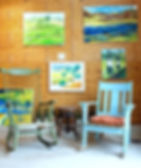 Two colorful rockingchairs in front o  collge of paintings inside the Mckenzie-Mueller tasting room