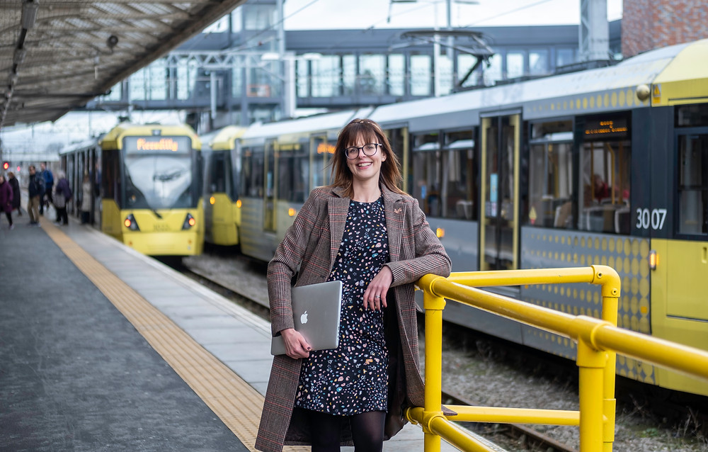 Business woman holding a macbook at a tram station