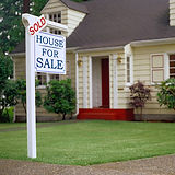 real estate sold sign in front of home