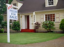For Sale Sign in front of a white painted home in