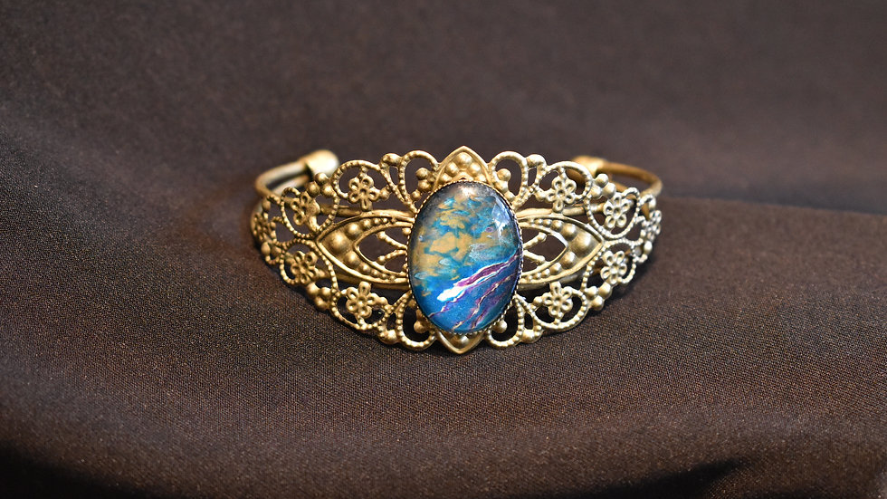 Filigree Gold setting with rich blues, purple, and golds