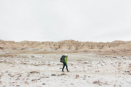 Person hiking, Badlands National Park, South Dakota, USA