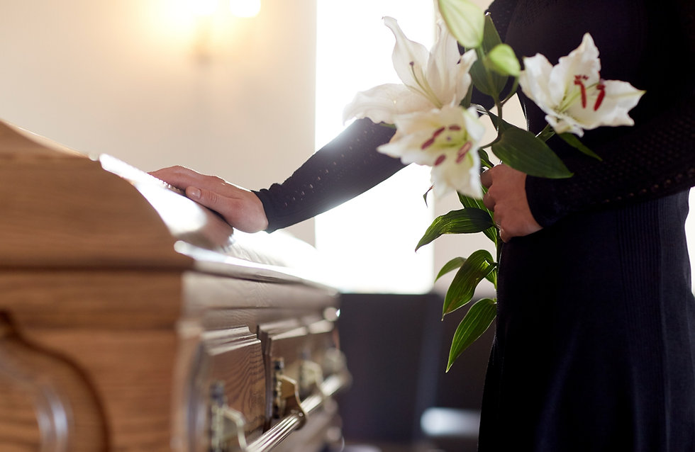 people and mourning concept - woman with white lily flowers and coffin at funeral in churc