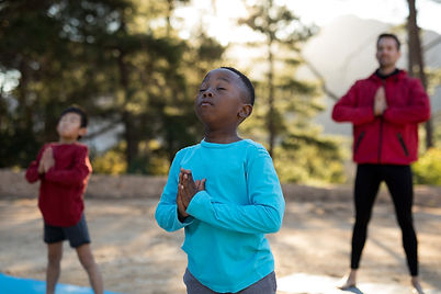 coach-and-kids-meditating-in-park-G2Q5KL