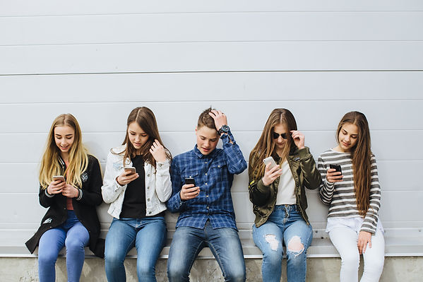 Group of teenagers sitting outdoors usin