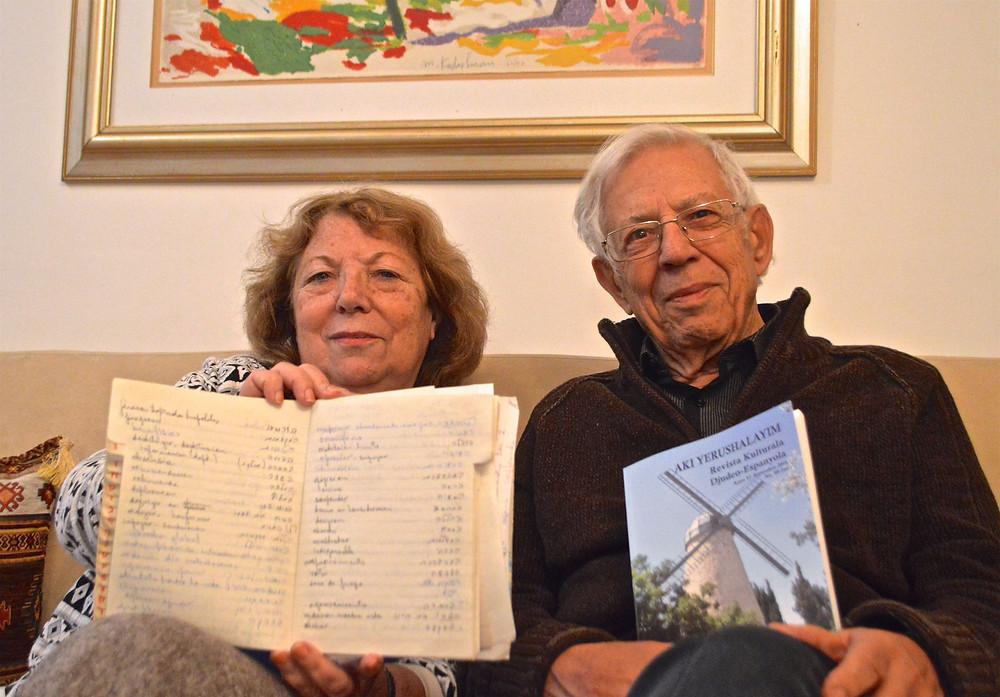 Zelda Ovadia y Moshe Shaul, editores de la revista. Ovadia sostiene un cuaderno con palabras en hebreo y ladino que recopiló durante sus años en La Bos de Israel. Abajo, los números 99-100, uno y 75.