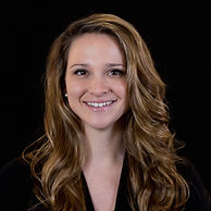 Headshot of Vice President of Admissions & Marketing Director Jackie Deiana, wearing a black blazer against a black background.