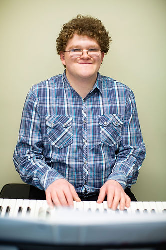 Photo of Mark, wearing a blue plaid botton-down shirt, smiling as he places his hands on the keyboard.