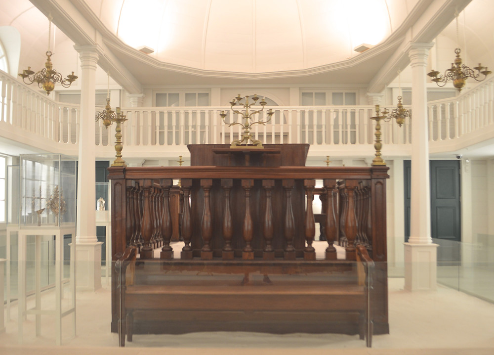 The bima, or teva, was made in Paramaribo in the 1800s. The women'a gallery of the Tzedek v'Shalom gallery is supported by 12 columns.