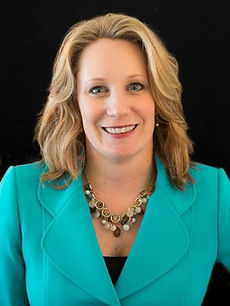Headshot of Executive Director Michelle Theroux wearing a teal blazer against a black background.
