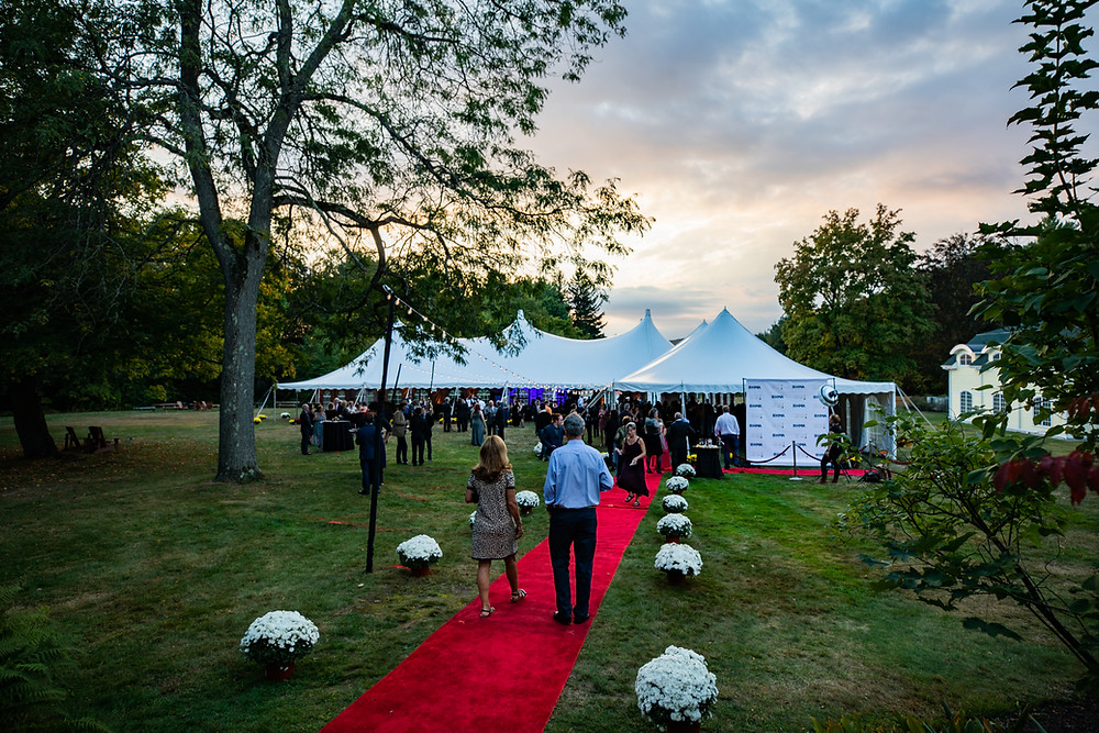 Image of a couple walking down the red carpet as they make their way to the tents set up in BHMA's backyard.