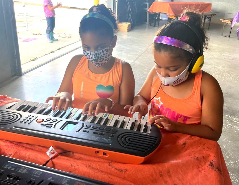 Sisters learning keyboard.