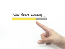 A finger pointing to a sign saying new start loading