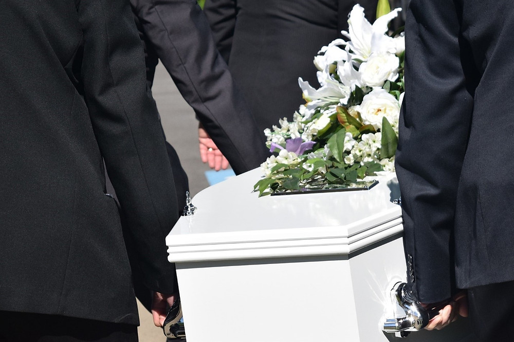 the bodies of three people carrying a white coffin dressed in black suits