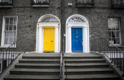 two semi-attached houses, one with a yellow door and one with a blue door