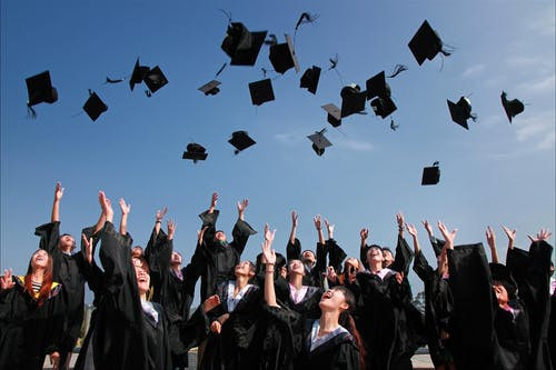 university students in their graduation gowns throwing their graduation caps in the air