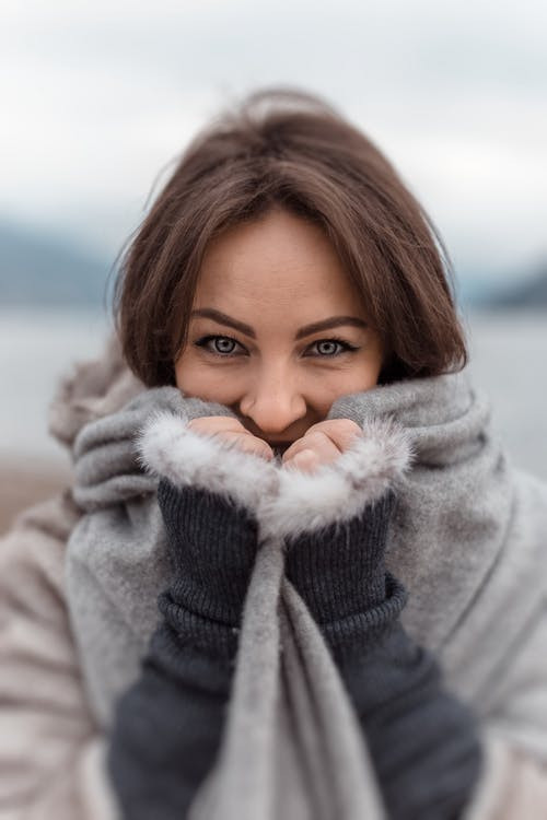 a woman wrapped up in a warm, grey, soft winter coat