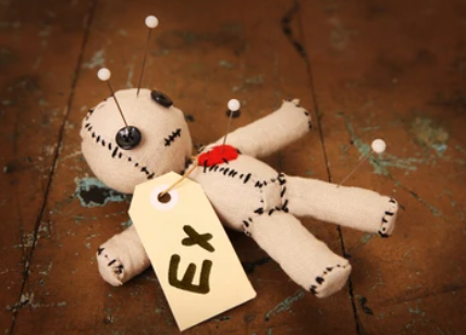 a voodoo style doll with pins stuck in it and a tag on it which says 'ex'