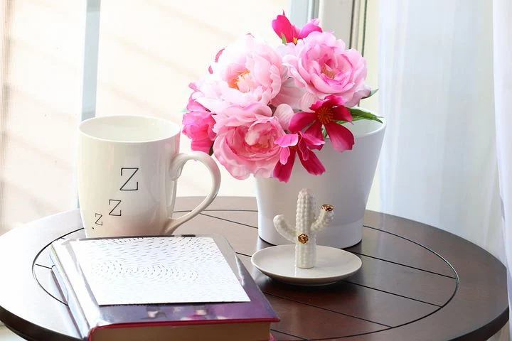 a vase of flowers, a cup of tea, a book, and a cactus