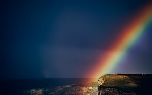 a rainbow going into the sea