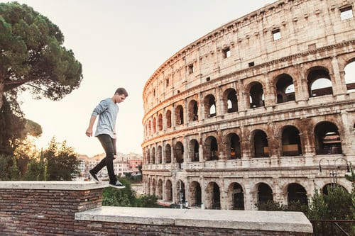 a man walking across a wall next to the Rome colosseum