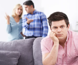 A son sat on the sofa whilst his Mum and Dad have an argument in the background