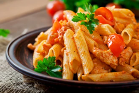 a black bowl of tomato pasta with some chicken and corriander
