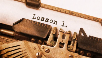 the top of a type writer. On the paper is typed out 'lesson 1'
