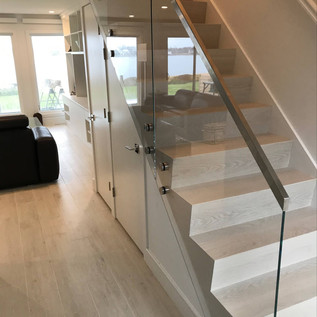 Starphire glass railing installed with standoffs and brushed stainless top cap