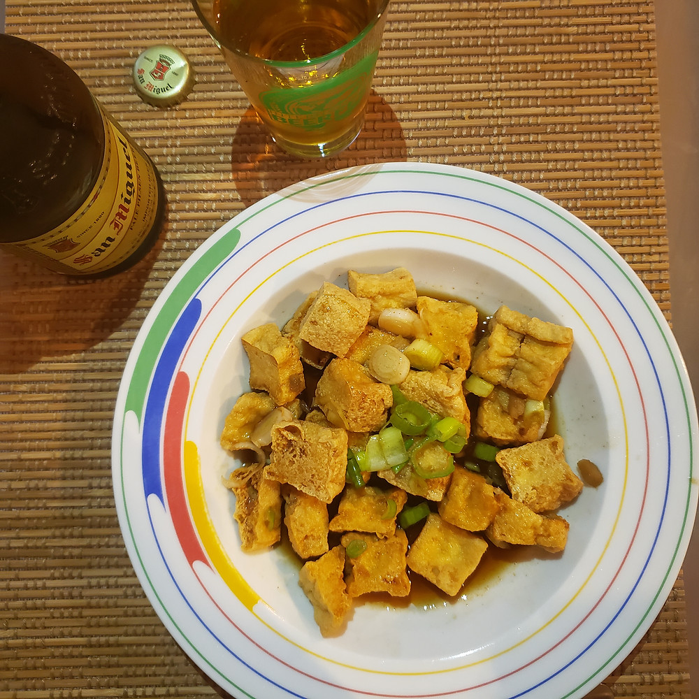 Fried Tokwa't Tokwa in sauce, sprinkled with green onions, and paired with San Miguel Pale Pilsen