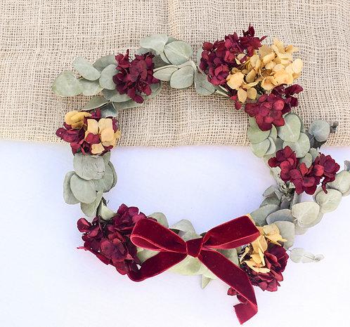 corona de flores preservadas con eucalipto y hortensias granates y mostaza