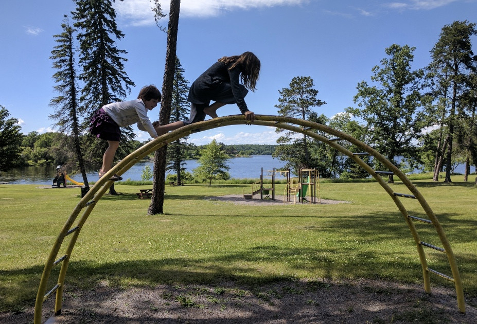 Two girls climbing a jungle gym at Lum Park Brainerd Minnesota