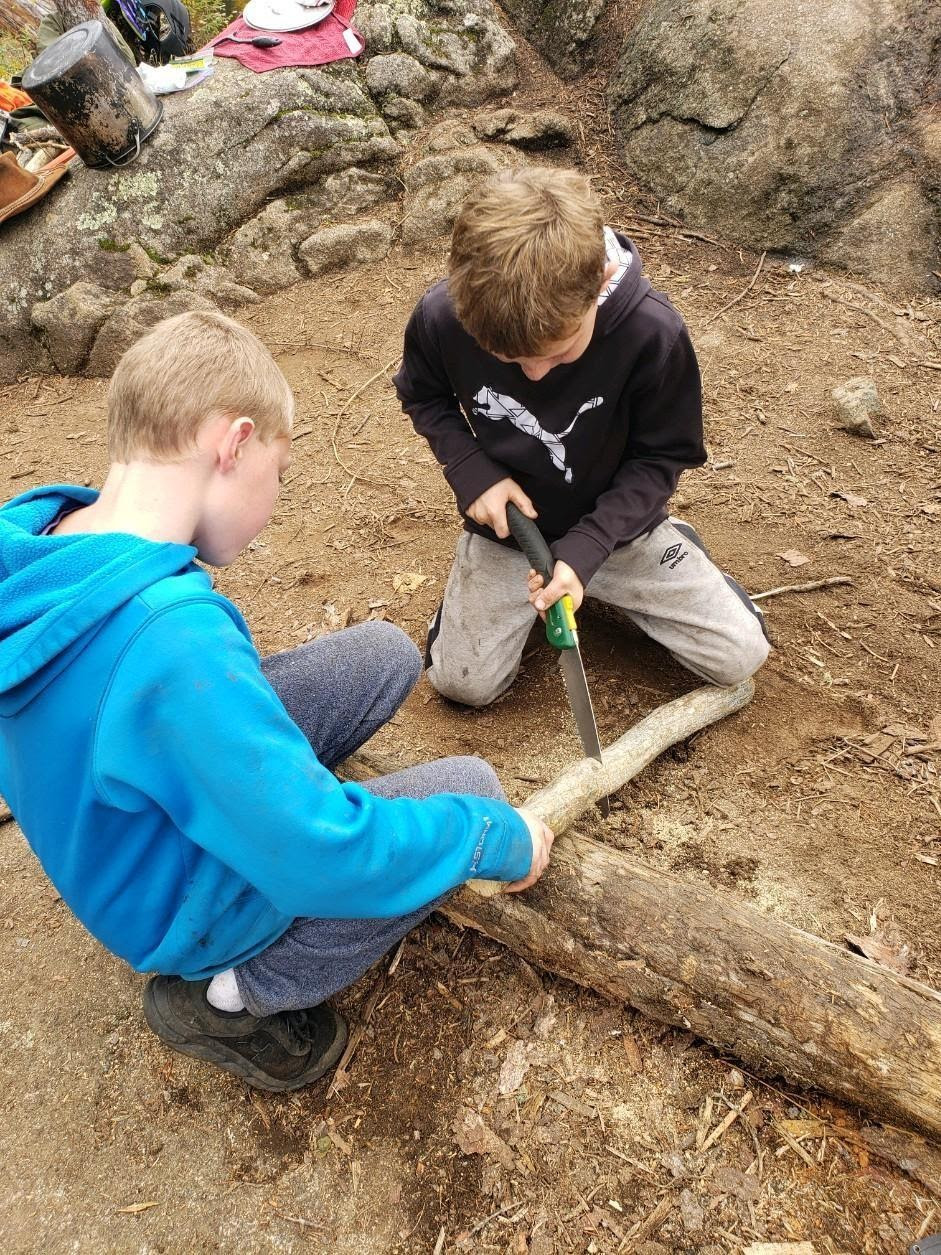 Two boys are cutting firewood in at a camp in the Boundary Waters Canoe Area