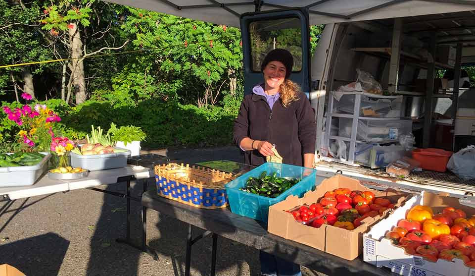 Rachel Cobb stands smiling behind many open boxes of fresh vegetables and flowers at the Nisswa Farmers Market