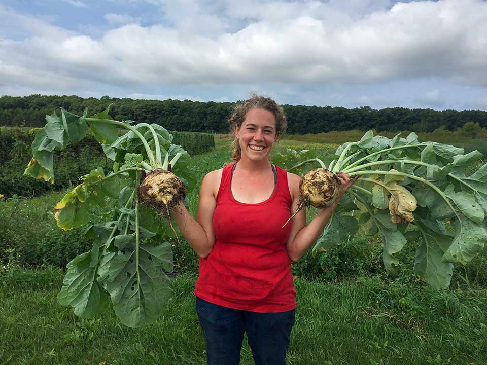 Rachel is showing off two giant turnips at her farm.