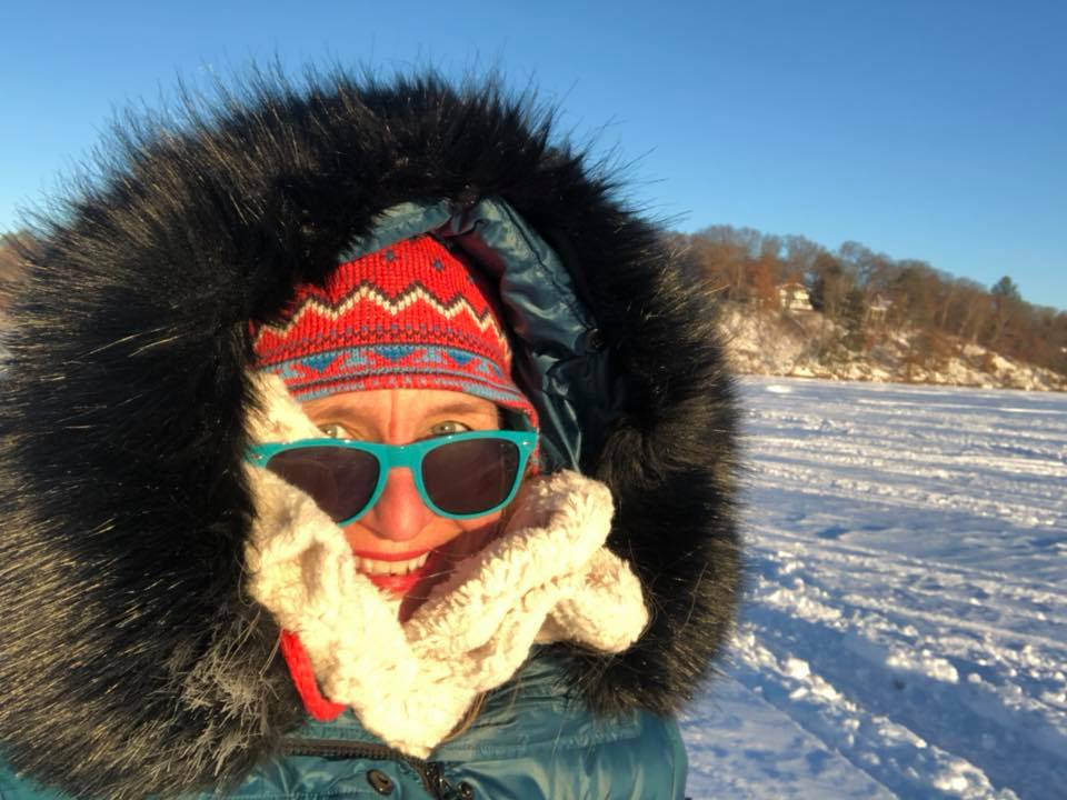 Amy Quarberg stepping out on the ice, wearing a fur-lined jacket, sunglasses, and a large smile.