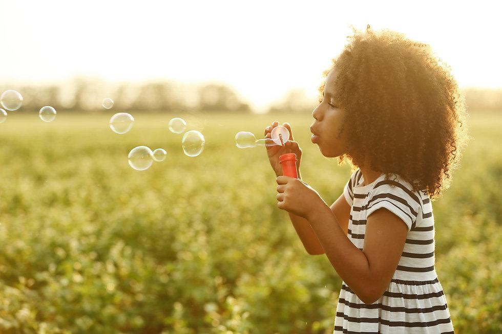 Little African American girl blowing bub