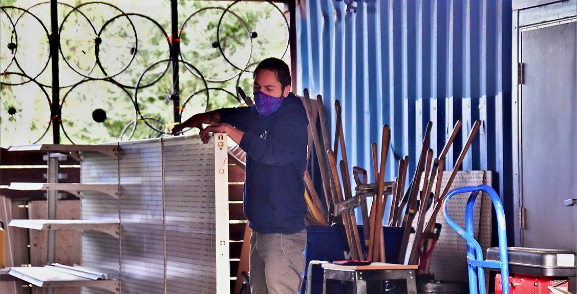 man building shelves at sktl