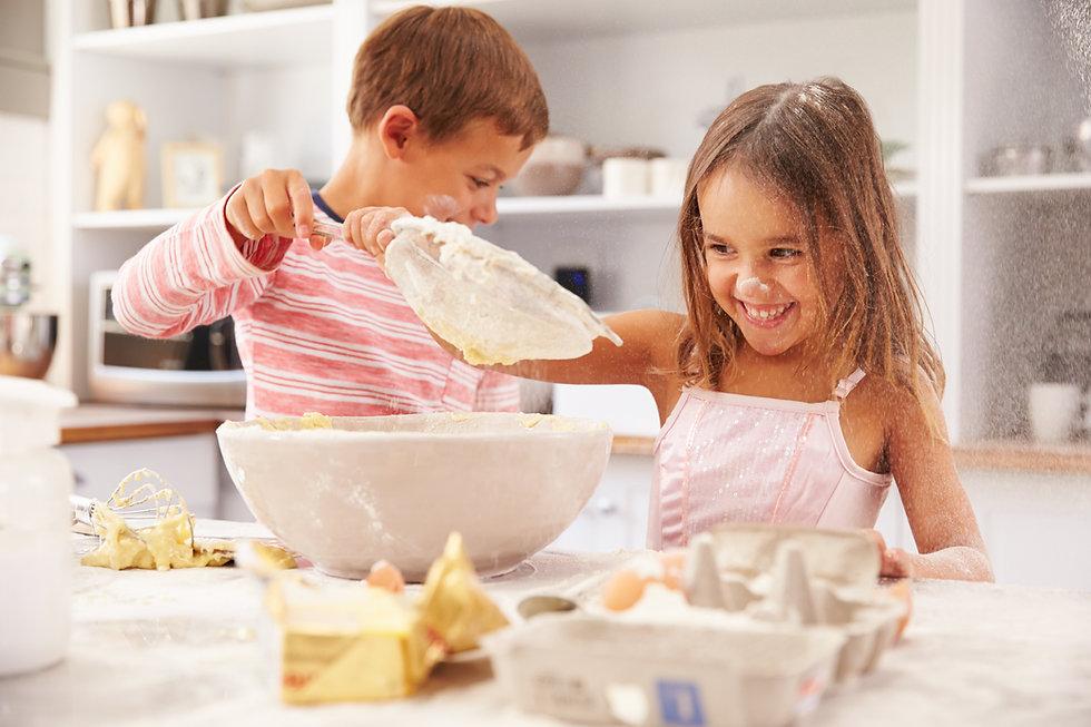 Two children having fun baking in the ki