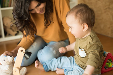 Smiling woman playing with baby on the floor