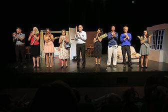 troupe de théâtre d'impro applaudissant en bord d'une scène de théâtre
