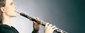 A oboe student playing the oboe in front of the teacher.