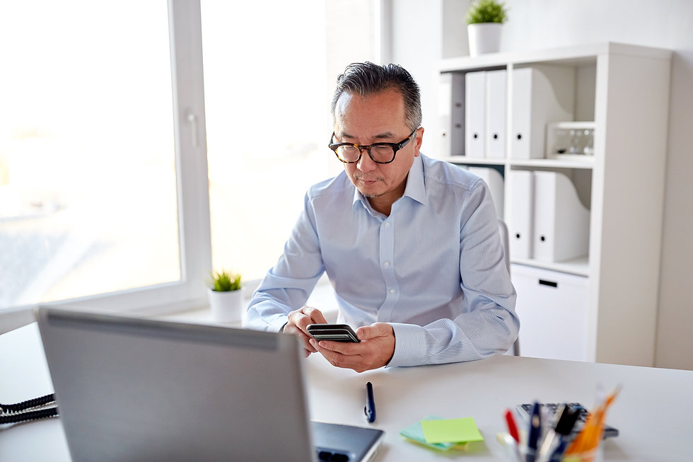 businessman-with-laptop-texting-on-smart