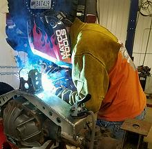 Man welding axle truss