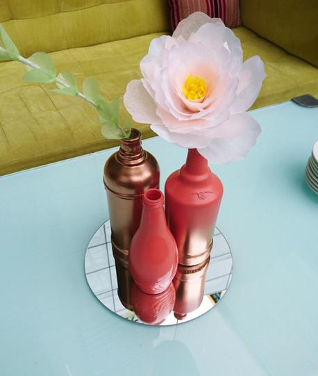 Centro de mesa con botellas y flores de papel